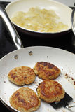 Cooking Four Turkey Patties and Onions. On a black glass stove top two pans are being used to cook dinner. In one pan are four turkey burgers cooking and in the stock image