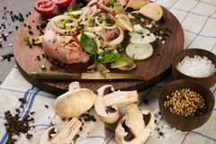 Cooking fresh chicken fillet with fresh vegetables. And spices seasoning on rustic wooden board. The table with the ingredients for the dishes. Dark stone Royalty Free Stock Image