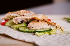 Cooking fresh homemade chicken wrap tortilla. On a wooden board Stock Image