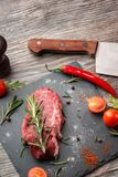 Cooking fresh meat. Beef steak with spices on slate board Royalty Free Stock Images
