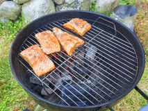 Cooking fresh salmon steaks on the grill, outdoors in summer stock images