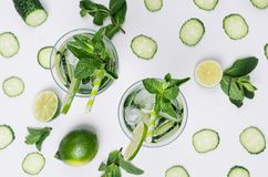 Cooking fresh summer organic drink with slices cucumber, ice, lime, mint, straw on white wood background, top view. royalty free stock photos