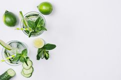 Cooking fresh summer organic drink with slices cucumber, ice, lime, mint, straw on white wood background, top view, copy space. Cooking fresh summer organic Stock Photos