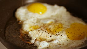 Cooking fried eggs with spice in frying pan for breakfast stock video footage