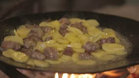 Fried Potatoes with Meal. Cooking fried potatoes with meal on a camping pan on a fire close-up stock video footage