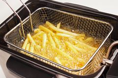 Cooking fries. Cooking french fries in deep fryer Stock Images