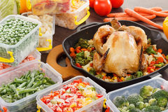 Cooking frozen vegetables and roasted chicken food. Cooking frozen vegetables in plastic containers, roasted chicken in pan. Healthy freezer food and meals Stock Images