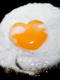 Cooking frying egg with heart shape yolk on black Royalty Free Stock Photo