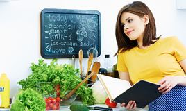 Cooking girl with recipe book. Beautiful smiling woman portrait in kitchen. Cooking girl with recipe book Royalty Free Stock Photo