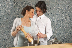 Cooking she gives him peper Stock Images