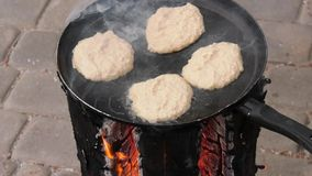 Potato pancakes, fried deep-fried in a pan over an open fire. stock footage