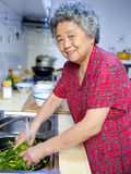 Cooking grandmother. A grandmother is cooking in kitchen Royalty Free Stock Photo