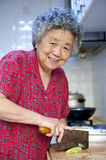 Cooking grandmother. A grandmother is cooking in kitchen Royalty Free Stock Image