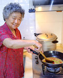 Cooking grandmother. Grandmother is cooking in kitchen Stock Images