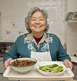 Cooking grandmother. A happy grandmother is cooking Royalty Free Stock Image
