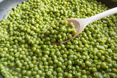 Cooking green peas in black frying pan with wooden spoon. Stewed vegetables with onion and others herbs Stock Image