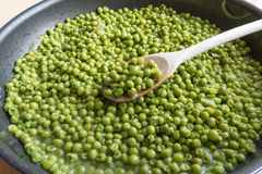 Cooking green peas in black frying pan with wooden spoon. Stewed vegetables with onion and others herbs Royalty Free Stock Image