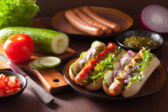 Cooking grilled hot dogs with vegetables ketchup mustard Royalty Free Stock Image