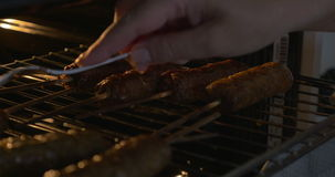 Cooking Grilled Sausages in Oven. Closeup shot of sausages on sticks hot oven. Someone is opening the oven door and turning them stock video footage