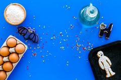 Cooking halloween gingerbread cookies concept. Glazed cookies, ingredients, crockery on blue background top view copy royalty free stock images