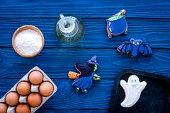 Cooking halloween gingerbread cookies concept. Glazed cookies, ingredients, crockery on blue wooden background top view royalty free stock images