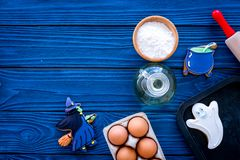Cooking halloween gingerbread cookies concept. Glazed cookies, ingredients, crockery on blue wooden background top view royalty free stock photo
