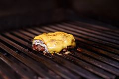 Chef making burger. Cooking hamburger. Beef or pork cutlet with cheese grilling on grid. stock image