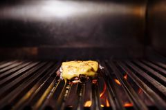 Chef making burger. Cooking hamburger. Beef or pork cutlet with cheese grilling on grid. stock photography