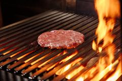 Chef making burger. Cooking hamburger. Beef or pork cutlet grilling on grid. stock photography