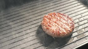 Cooking hamburger. Beef or pork cutlet grilling on grid. Slow motion. HD stock video footage