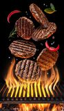 Cooking Hamburger cutlet. Conceptual picture. Steak with spices and cutlery under burning grill grate royalty free stock image