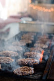 Cooking Hamburgers on the Grill. A large number of hamburger patties are grilled over an open flame Stock Image