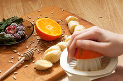 Cooking,hand squeezes orange juice, banana,frozen strawberries blackberries and seeds vivid smoothie ingredients and blender, juic. Er, tulips on the background royalty free stock photography