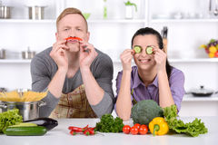 Cooking. Happy Couple  Together - Man and Woman in their Kitchen at home Preparing Vegetable Salad. Diet. Dieting. Healthy Food Royalty Free Stock Photo