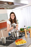 Cooking - Happy woman cook in modern kitchen Royalty Free Stock Images