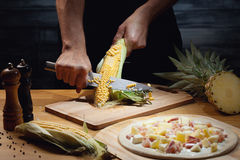 Cooking hawaiian pizza. Chef cooking hawaiian pizza, cutting fresh corn. Low key shot, close up of hands, some ingredients around on table Royalty Free Stock Photo