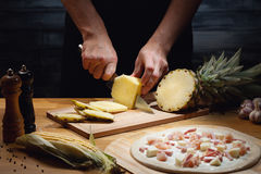 Cooking hawaiian pizza. Chef cooking hawaiian pizza, cutting fresh pineapple. Low key shot, close up of hands, some ingredients around on table royalty free stock photography