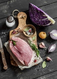 Cooking healthy food - meat, red cabbage, spices and herbs. Raw ingredients. On a dark wooden background stock photo