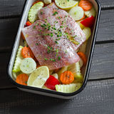 Cooking healthy food - raw ingredients: potatoes, zucchini, carrots, onions, garlic, peppers and fish sea bass in a baking dish Royalty Free Stock Photos