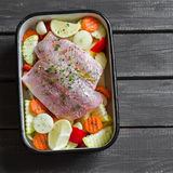 Cooking healthy food - raw ingredients: potatoes, zucchini, carrots, onions, garlic, peppers and fish sea bass in a baking dish Royalty Free Stock Image