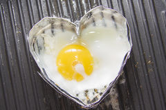 Cooking heart shaped fried eggs Royalty Free Stock Images