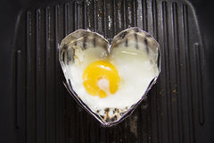 Cooking heart shaped fried eggs Royalty Free Stock Photography