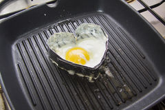 Cooking heart shaped fried eggs Stock Photos