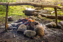 Cooking in a hike in the cauldron hanging over the fire. From the boiler coming white smoke stock photo