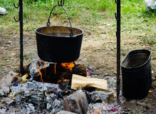 Cooking in a hike in the cauldron hanging over the fire Stock Photography
