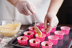 Cooking and home concept - close up of hand filling muffins mold Stock Photos