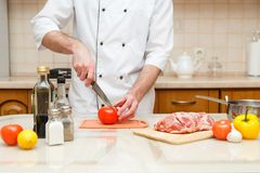 Cooking and home concept - close up of male hand cutting tomato on cutting board with sharp knife. Cooking and home concept - close up of male hand cutting Stock Photos