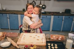 Cooking homemade cakes. Happy loving family are preparing bakery together. Mother and child daughter girl are cooking. Cookies and having fun in the kitchen stock photography