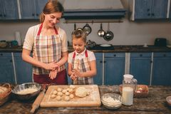Cooking homemade cakes. Happy loving family are preparing bakery together. Mother and child daughter girl are cooking. Cookies and having fun in the kitchen stock image