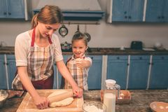 Cooking homemade cakes. Happy loving family are preparing bakery together. Mother and child daughter girl are cooking. Cookies and having fun in the kitchen royalty free stock images